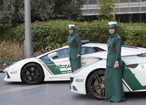 Dubai policewomen pictured with two vehicles in the force's supercar fleet.